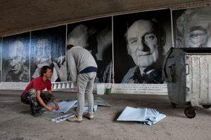 Fotograf Šymon Kliman prelepuje plagáty zo svojich fotografií účastníkov SNP pod mostom SNP v Bratislave v auguste 2012.