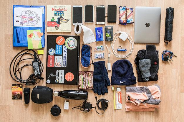 Zložka na dokumenty, kresby od dcéry zo škôlky, kniha, ktorú dcére číta počas jazdy električkou, štyri mobilné telefóny, horalky, kakaové rezy, dáždnik, dva laptopy s adaptérmi, kľúče, extra spodná bielizeň a ponožky, rukavice, adaptér, klobúk, tričko, zubná kefka a pasta, deodorant, vreckovky, toaletný papier, adaptéry, 3 USB nabíjačky, USB, SD karty a slúchadlá, štuple do uší, škraboška na spanie, malé svetlo, baterky, antireflexný pásik, pas v taške, fľaša, nabíjačka.