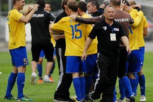 Myjava má právo hrať medzi slovenskou futbalovou elitou. Tréner Hudec (v popredí v čiernom) oslavuje s hráčmi.