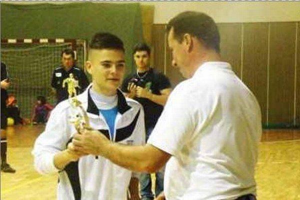Ján Komora z víťazného celku FK Šurany preberá ocenenie za najlepšieho hráča turnaja z rúk Mariána Pechu.