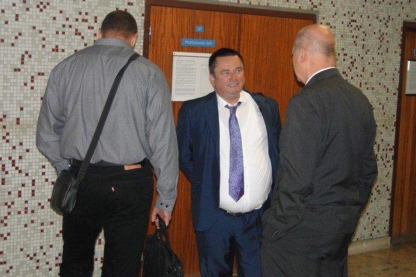 Matúš Grega (vľavo) na okresnom súde. Objektívu fotoaparátu sa obrátil chrbtom. V strede Gregov obhajca Jaroslav Homza.