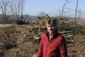 Nový starosta Smrčo. Vľavo za ním je holorub a popílené drevo. Vpravo vzadu sú topole, z ktorých časť už tiež padla napriek pozastaveniu výrubu.