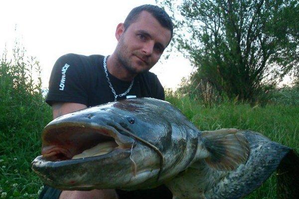 Rybár s úlovkom. Sumca pustil späť do vody.