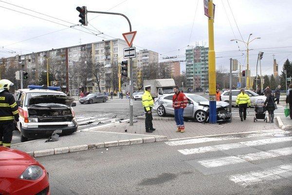 Po nehode. Osobné auto skončilo v stĺpe, sanitka so zlomenou nápravou.