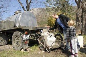 Ľudia si vodu naberajú do bandasiek či iných nádob z cisterny.