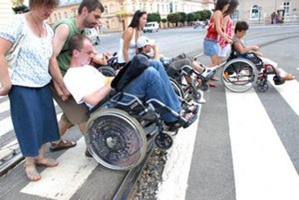 Prechod cez Námestie maratónu mieru. Vozičkár tam sám cez koľajnice neprejde. Potrebuje pomoc osobného asistenta. Ak máte viac ako 80 kg, a on je slabší, nastáva preňho problém a pre vozičkára tiež.