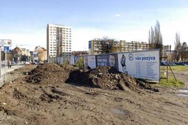 Rozbahnený pozemok. Prechádzajú po ňom ťažké mechanizmy, víriace prach alebo roznášajúce blato. Kopa stavebného odpadu medzičasom zmizla.