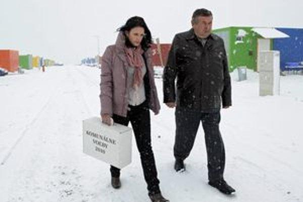 Členka volebnej komisie Iveta Dulovičová (vľavo) s prenosnou urnou a podpredseda komisie Bartolomei Marton (vpravo) v Nižnej Myšli na kontajnerovom sídlisku, ktoré vybudovali v obci po povodniach a zosuvoch pôdy.