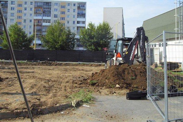 Pozemok. Zmizla tráva, mechanizmy upravujú plochu.