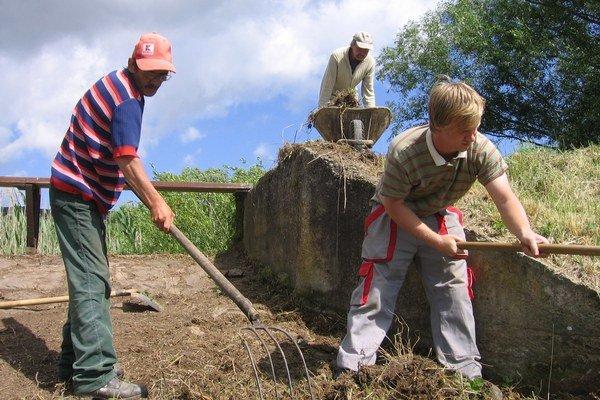 Obecní zamestnanci pracujú na čistení kamenných priepustov medzi rybníkmi.