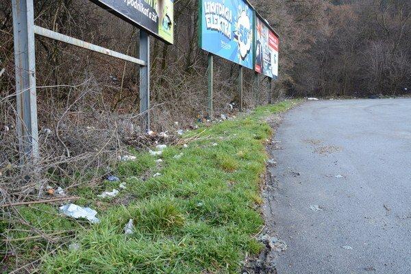 Okolie parkoviska. Odpadky sú rozhádzané všade navôkol.