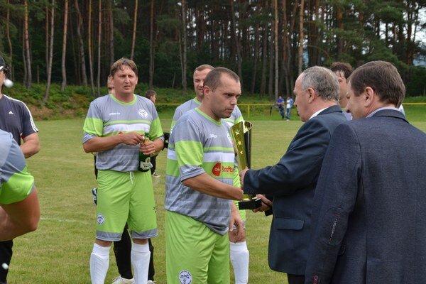 Pohár. Kapitán FK Krásnohorské Podhradie preberá pohár pre víťaza V. ligy.