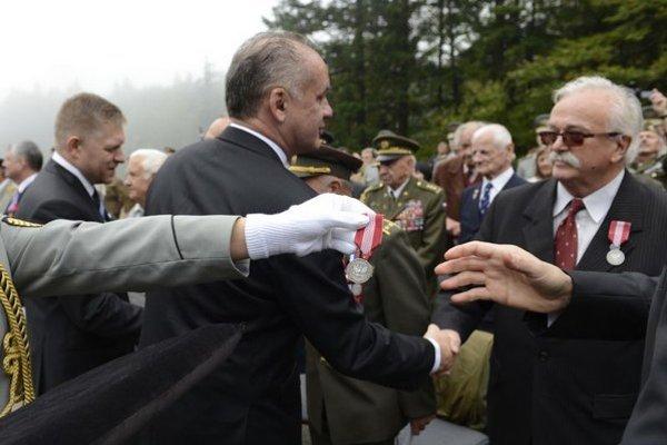 Na snímke uprostred prezident SR Andrej Kiska a vľavo predseda vlády SR Robert Fico zdravia ocenených účastníkov pietneho aktu.