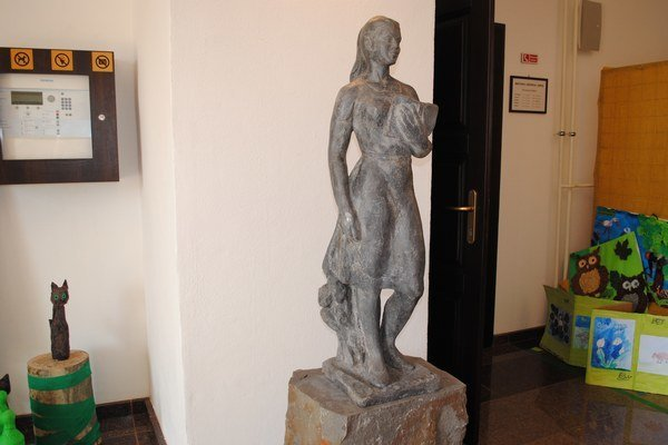 Plastika Dievča s knihou. Je vo vstupnej hale kaštieľa pred vstupom do mestskej knižnice.