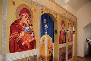 Ikonostas. Na murovanej stene sú nalepené na plátne tlačené ikony.