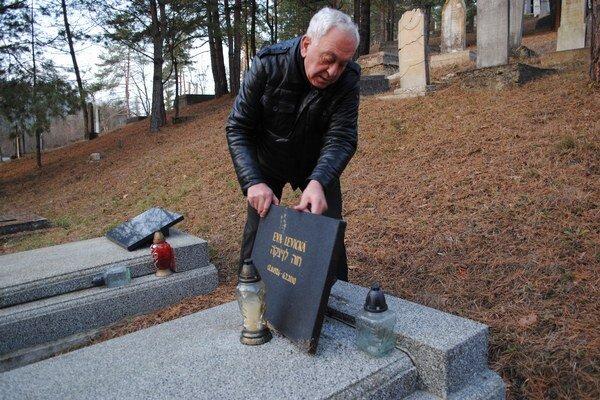Pri hrobe matky. Juraj Levický kontroluje odlepenú tabuľu z hrobu svojej matky.