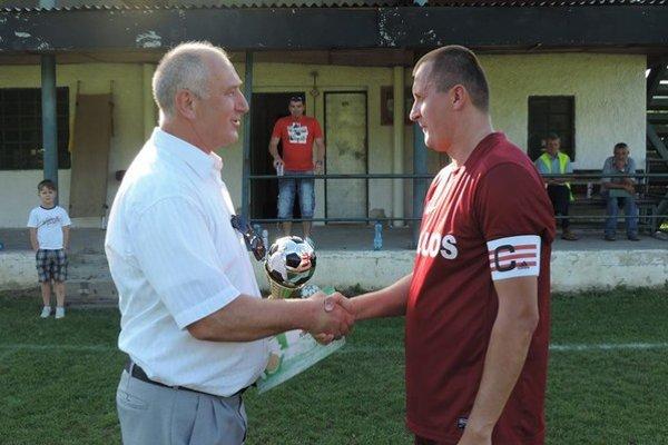 Blahoželanie víťazovi. Milan Kováč, člen Výkonného výboru ObFZ Humenné, odovzdáva trofej pre víťaza I. triedy 2013/2014 do rúk Mareka Čerňu, kapitána FK Humenné.