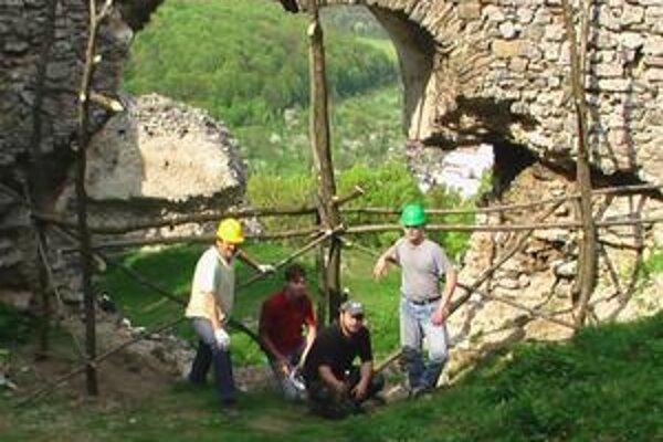 Dobrovoľníci. Vo vstupnom portáli horného hradu postavili lešenie. Fotografia je z 1. mája tohto roku.