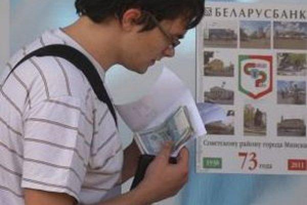 Mladý muž počíta svoje peniaze  pred zmenárňou v bieloruskej metropole Minsk.