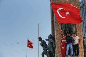 Ľudia stojaci na pamätníku na námestí Taksim v Istanbule držia turecké vlajky.