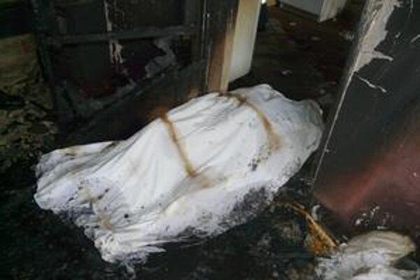 Miesto požiaru. Bezvládne telo dôchodkyne našli záchranári na zemi.