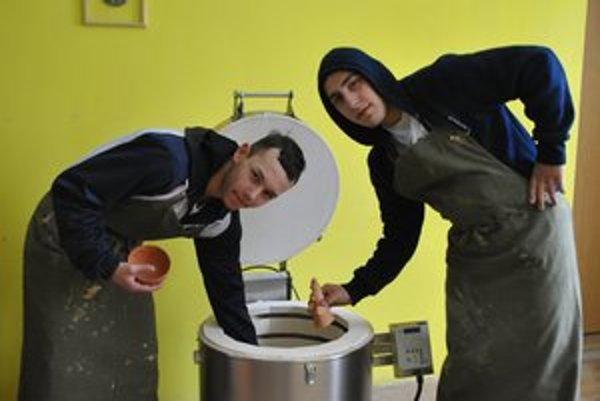 Števko a Janík. Keramika ich baví. Z pece vyberajú čerstvé výpalky.