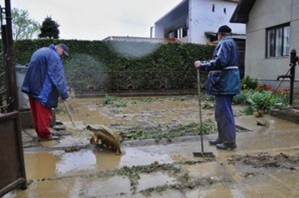 Muži odstraňujú blato z dvora rodinného domu po intenzívnej búrke v Smižanoch.