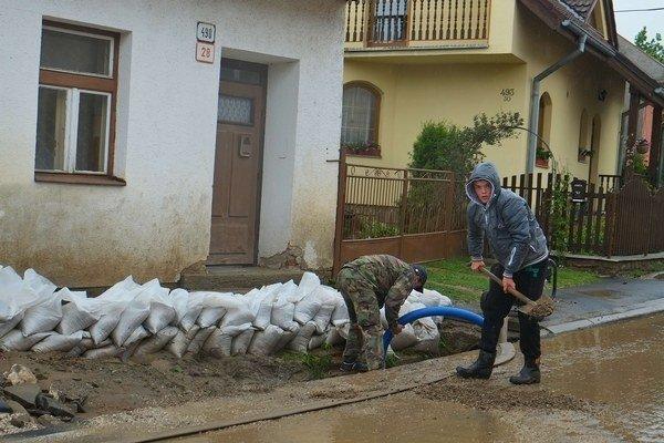 Chlapec odstraňuje nánosy bahna spred domu v mestskej časti Popradu - Stráže po silnej búrke.