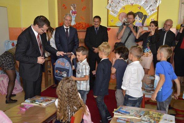 Minister školstva odovzdáva školské pomôcky prvákom počas otvorenia školského roka na základnej škole Grundschule v Kežmarku.