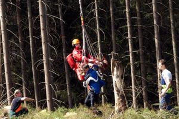 Nedostupný terén. Slavomír Kállay po základnom ošetrení v podväze vrtuľníka prenáša pacienta.