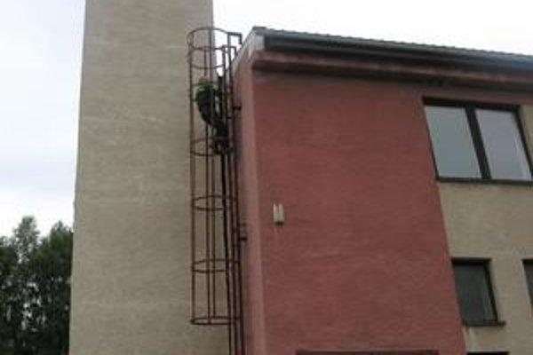 V dolnej časti je veža spätá so stenou hasičskej budovy. Hore sa však odchyľuje o niekoľko centimetrov.