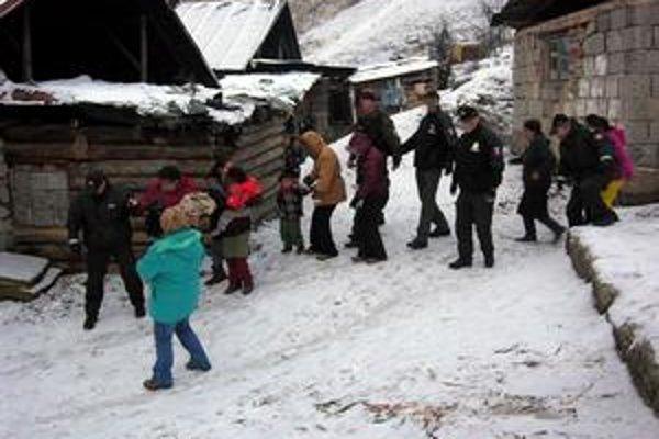 Sociálni pracovníci. Vynášajú malé deti na rukách. Pred davom ich ochraňovali policajti.