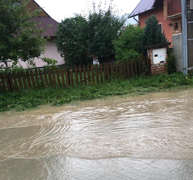 Voda sa hrnula z cesty aj do rodinných domov.