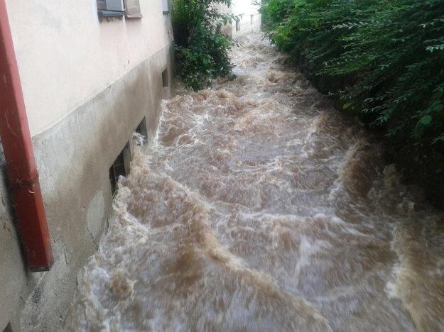 V centre Kremnice. Voda sa dostala do pivnice bytového domu, ktorý susedí priamo s potokom.