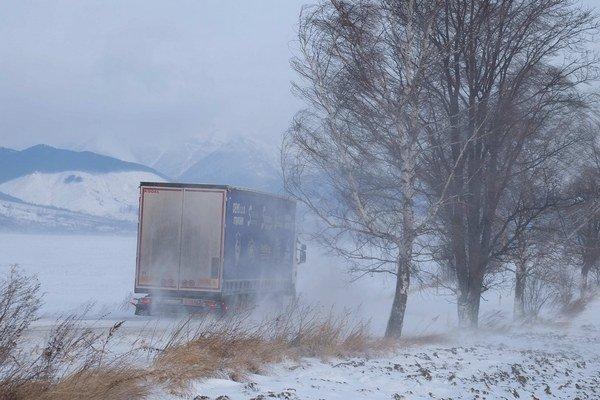 Autá prechádzajú po ceste III. triedy medzi Popradom a Veľkým Slavkovom počas silného vetra.