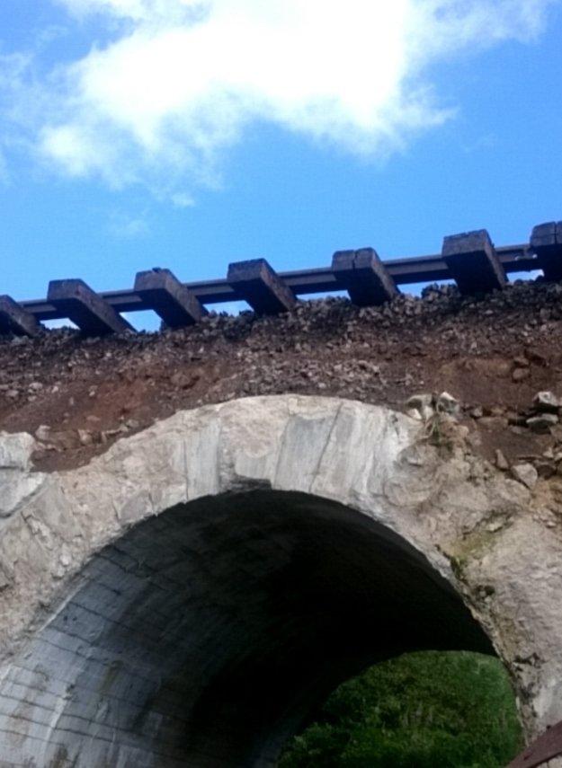Poškodená časť mosta a odkryté koľajnice.