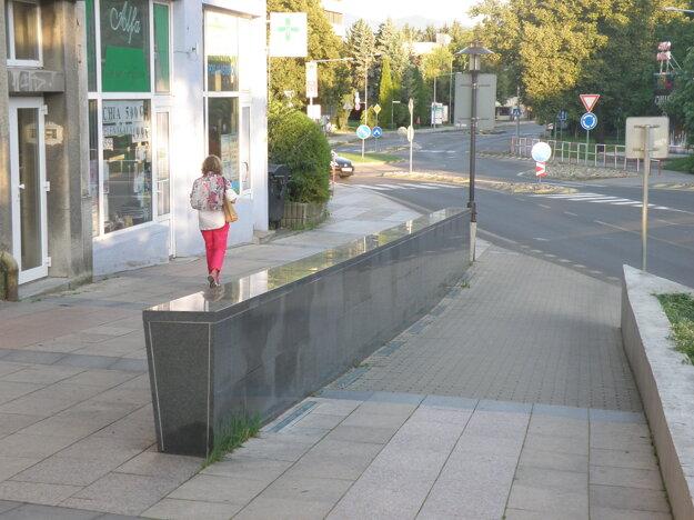 Malý múrik oddeľuje chodník od cesty pre zásobovacie vozidlá.