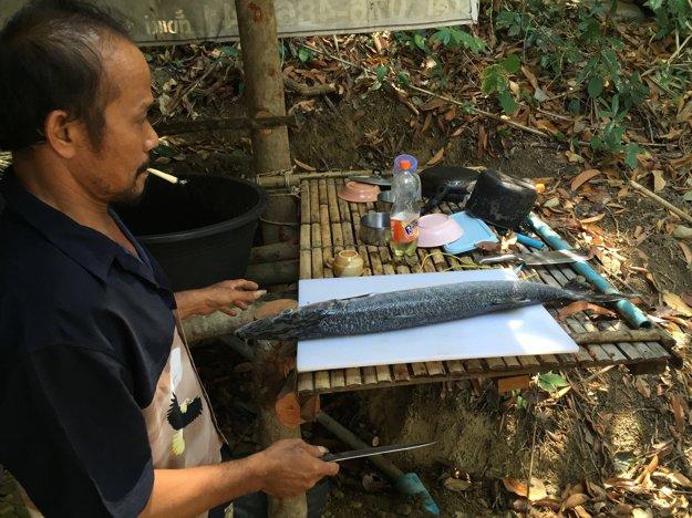 Thajský sprievodca čistí práve ulovenú barakudu na maličkom ostrove Koh Ra.
