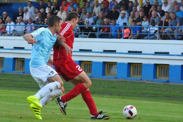 Lukáš Rupec z Malaciek (v červenom)  zachraňuje pred hosťujúcim Tomášom Hrutkom (Most).