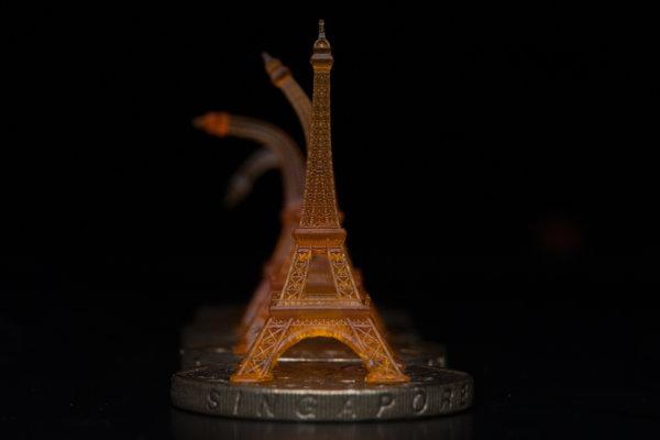 Ohnutá replika Eiffelovej veže sa vracia späť do pôvodného tvaru na zohriatej singapurskej minci.