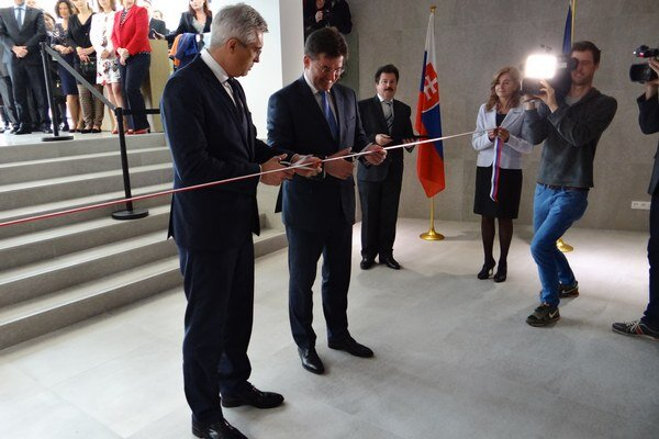 Pásku na novej budove slávnostne prestrihol slovenský minister zahraničných vecí Miroslav Lajčák a šéf slovenského zastúpenia Ivan Korčok.