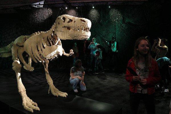 Diváci sledujú sochu tyranosaura počas výstavy v Paríži.