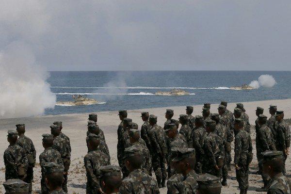 Filipínski vojaci pozorujú vylodenie amerických vojakov.