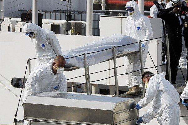 Príslušníci talianskej pobrežnej stráže počas vylodenia mŕtveho tela. Pri utečeneckej dráme v Stredozemnom mori až 700 ľudí zahynulo po tom, ako sa v noci zo soboty na nedeľu prevrátila loď s utečencami na palube.