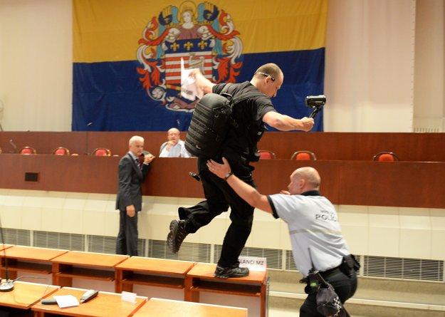 Mestský policajt zasahuje v rokovacej miestnosti proti nespokojnému občanovi.