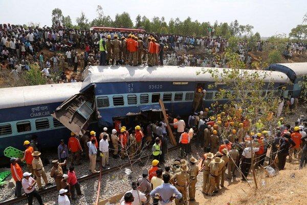 Záchranári zo zdemolovaného vlaku vyťahujú uviaznutých ľudí.