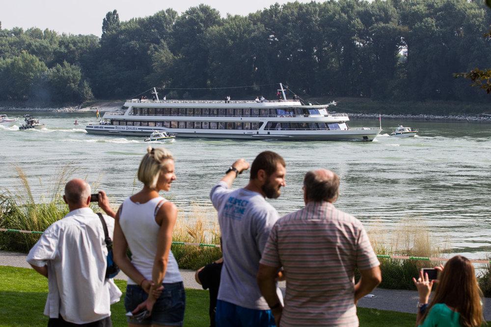 Ľudia pozorujú príchod lode s lídrami EÚ.