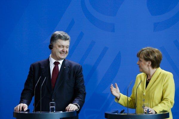 Nemecká kancelárka Angela Merkelová (na snímke vpravo) a ukrajinský prezident Petro Porošenko (vľavo) počas tlačovej konferencie po spoločnom rokovaní v Berlíne.