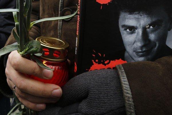 Žena drží sviečku a časopis s fotografiou Borisa Nemcova počas rozlúčky v Moskve.
