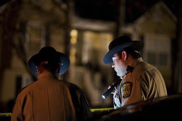 Polícia stojí pred domom, v ktorom sa odohrala streľba.